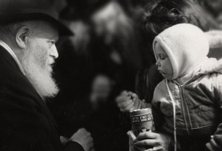 The Rebbe waits as a child places a coin that the Rebbe just gave him into a charity box that his mother is holding. (Photo: Algemeiner Journal/Lubavitch Archives)