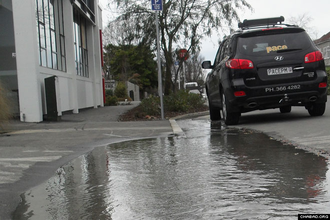 Ruptured water mains and sewer lines left puddles all over streets in and around Canterbury, New Zealand, such as in front of the home belonging to Chabad-Lubavitch Rabbi Mendel and Sara Goldstein.