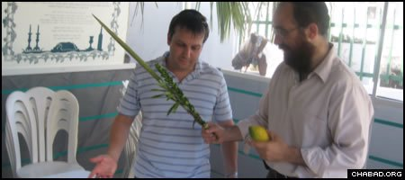 Chabad-Lubavitch Rabbi Mendel Zarchi helps a Jewish visitor make a blessing on the Four Species inside his sukkah in Puerto Rico.