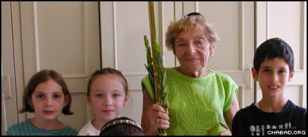 Jewish children in S. Jose, Costa Rica, help a women make a blessing on the traditional Sukkot combination of a palm branch, myrtle twigs, willow branches and a citron, known as the Four Species.