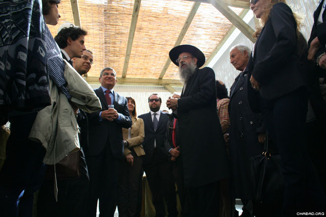 """Chabad-Lubavitch of Rome director Rabbi Yitzchak Hazan welcomes officials to the """"Sukkah of Peace"""" erected for the Jewish holiday of Sukkot at the city's Piazza Farnese."""