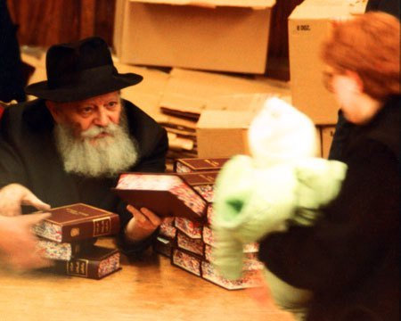 The Rebbe hands a Tanya, the fundamental text of Chabad philosophy, to a small child held in his mother's hands (Photo: Lubavitch Archives).