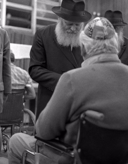 The Rebbe hands a dollar to a wounded Israeli, for him to give to charity. Photo: Yossi Melamed