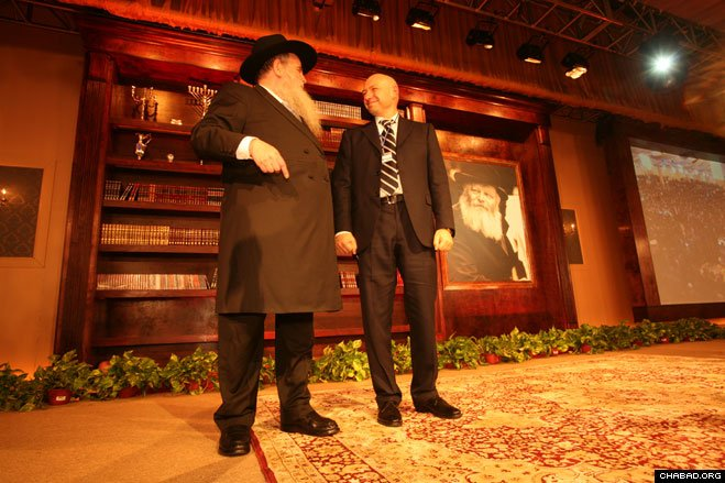 Rabbi Moshe Kotlarsky, director of the International Conference of Chabad-Lubavitch Emissaries and vice chairman of Merkos L'Inyonei Chinuch, the educational arm of Chabad-Lubavitch, and Ukraine billionaire philanthropist Gennady Bogolubov glance at a banquet-hall full of 4,500 dancing guests at the 27th annual conference's gala banquet Sunday night.