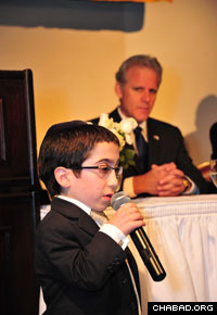 Shmuly Brafman, a student at the elementary school affiliated with the Rabbinical College of America in Morristown, N.J., entertains the crowd at the institution's 40th anniversary dinner as Israeli Ambassador Michael B. Oren listens to the performance. (Photo: Michael Livshin)