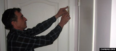 A Jewish resident of the Canadian province of Saskatchewan affixes a mezuzah to his doorpost after meeting with Chabad-Lubavitch Rabbi Raphael Kats.