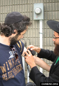Rabbi Raphael Kats, who will soon open the first Chabad House in Saskatchewan, helps a student don the Jewish prayer boxes known as tefillin.