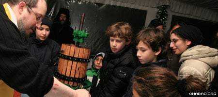 Rabbi Meir Ossey from Chabad of the Upper West Side shows area children how olive oil is made.
