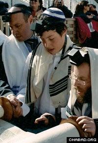 Rabbi Mendel Deren reads from the Torah at the Bar Mitzvah of Allen Mekibel at Jerusalem's Western Wall.