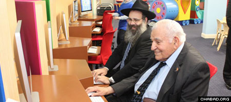 Rabbi Zalman Wolowik and Cedarhurst, N.Y., Mayor Andrew J. Parise check out the computer lab at the just-opened Levi Yitzchak Jewish Children's Library. (Photo: Levi Stein)