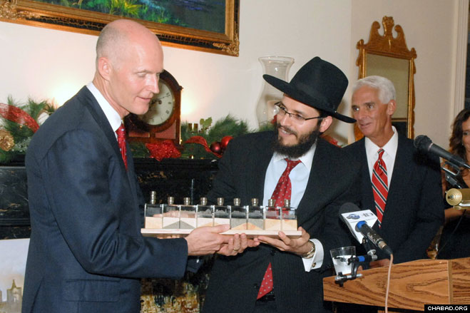 Rabbi Schneur Oirechman, director of Chabad-Lubavitch of Tallahassee, presents a Chanukah menorah to Florida Governor-elect Rick Scott at the Governor's Mansion in the state capital. Both Scott and outgoing Gov. Charlie Crist hosted a Jewish delegation for a pre-Chanukah party on Monday.