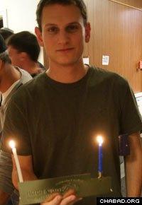 An AEPi brother proudly displays his Chanukah menorah.