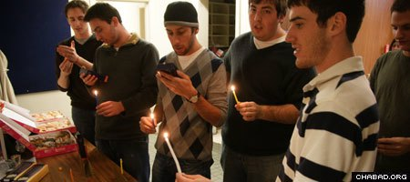 Fraternity brothers at the Northwestern University chapter of Alpha Epsilon Pi celebrate Chanukah with a menorah lighting kit provided by the Chabad on Campus International Foundation.