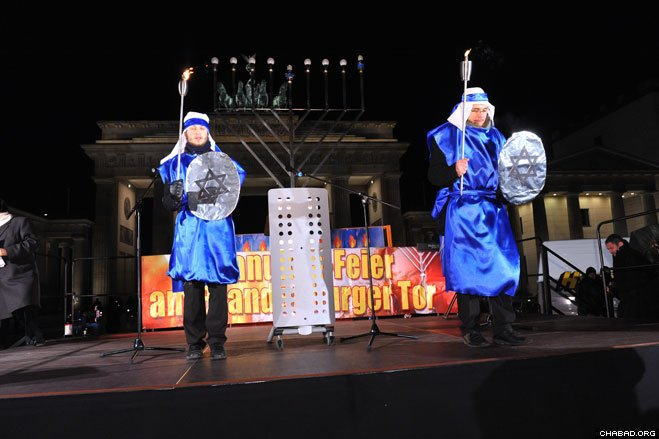 Costumed actors put on a production of the Chanukah story at the public menorah lighting at Berlin's Brandenburg Gate. Organized by Chabad-Lubavitch of Berlin in conjunction with the Israeli Embassy, the Jewish National Fund, the World Zionist Organization, the Central Council of Jews in Germany, B'nai B'rith, and other organizations, the celebration included U.S Ambassador Philip Murphy, Bundestag vice president Petra Pau, and a representative from the local municipality.
