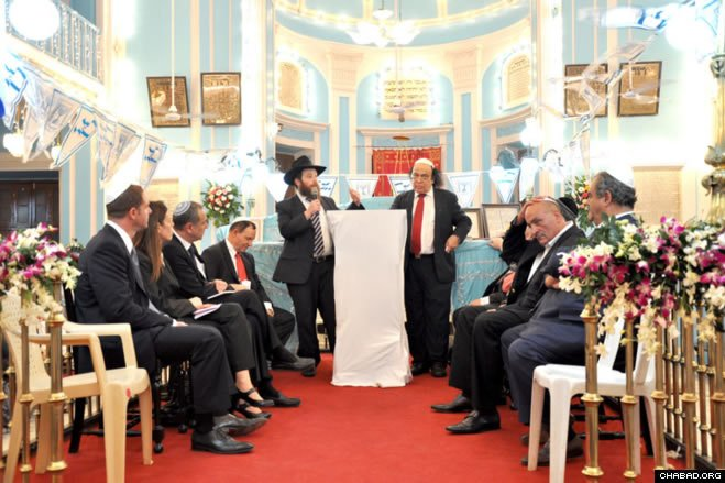 Chabad-Lubavitch of Mumbai director Rabbi Chanoch Gechtman, center left, and local Jewish community leader Solomon Sopher talked about the importance of Chanukah for a delegation of dignitaries at the Indian financial capital's historic Knesset Eliyahu synagogue.