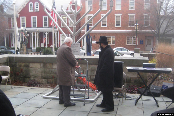 Blair County Sheriff Mitch Cooper helps light the Chanukah menorah with Rabbi Yossi Stein, director of the Chabad-Lubavitch Jewish Center of Greater Altoona, Pa.
