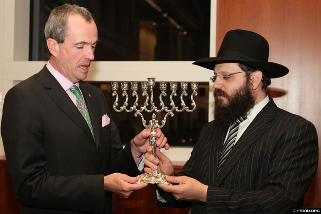U.S. Ambassador Philip D. Murphy received a menorah from Chabad-Lubavitch Rabbi Yehuda Tiechtel at a reception honoring the public menorah lighting at Berlin's Brandenburg Gate.