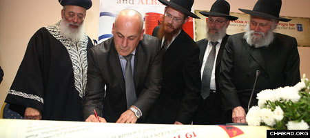 Jewish community leaders in Tirana, Albania, sign a document appointing Chabad-Lubavitch Rabbi Yoel Kaplan of Thessaloniki, Greece, as the country's first chief rabbi. (Photos: Meir Alfasi)