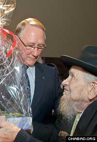 "Mayor Gerald Tremblay receives a menorah from Rabbi Menachem Zeev ""Wolf"" Greenglass at a Chanukah celebration in city hall. (Photo: Menachem Serraf)"