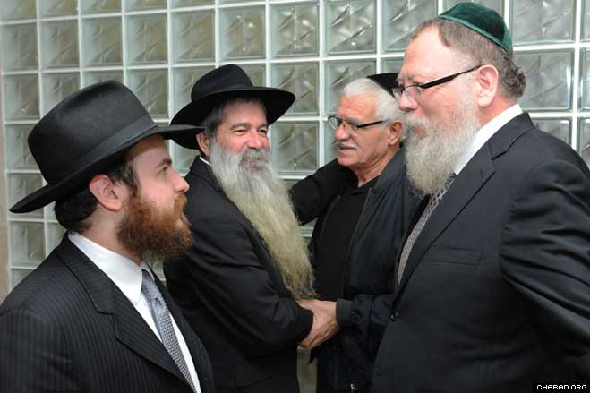 Chabad-Lubavitch Rabbi Mendy Mathless, left, who gave one of his kidneys to Yisrael Konstantini, second from left, chats with Rabbi Avrohom Lider, the Brooklyn, N.Y., rabbi who made the donation possible, at a Jan. 10 celebratory dinner in Konstantini's hometown of Netanya, Israel.