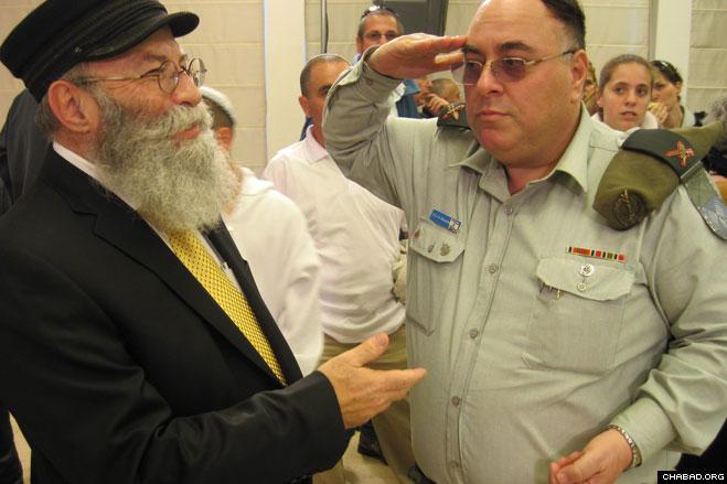 Rabbi Yaakov Gloiberman, director of the Chabad-Lubavitch run Yad B'Yad charity, greets Israel Defense Force spokesman Brig. Gen. Avi Benayahu at the Tel Aviv ceremony celebrating the promotion of Maj. Gen. Benny Gantz as the army's 20th chief of staff.