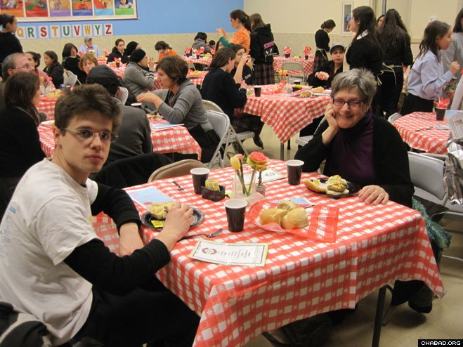 Jewish community members enjoy a restaurant-style dinner conceived, planned and executed by the female volunteers associated with the Friendship Circle of Cleveland's Teen Scene.