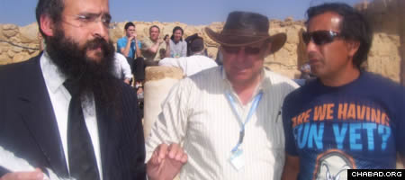 Rabbi Shimon Elharar presents a quill pen used by a ritual scribe atop the ancient Israeli desert fortress of Masada to Raul Bustos, leader of the trapped Chilean miners who were rescued in 2010.