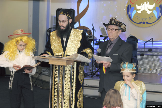 Chabad-Lubavitch Rabbi Levi Mondshine, chief rabbi of the Smolensk region, reads from the Scroll of Esther during a Purim celebration at the Russian city's 7/40 restaurant.