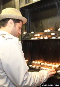 Yigal Dakar lights a candle before entering the Rebbe's resting place.