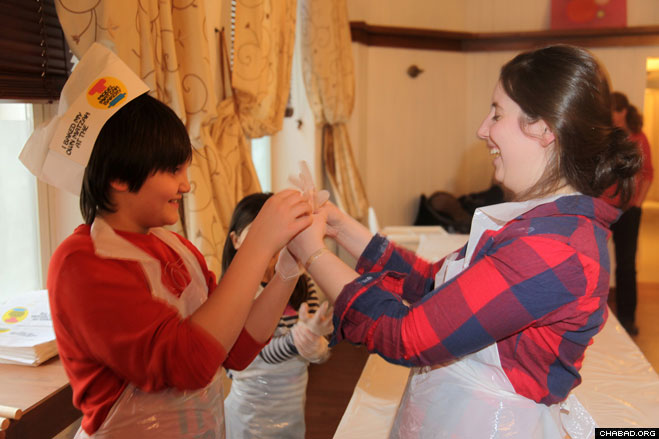 Jewish children don latex gloves before working with the flour and water that will become matzah.