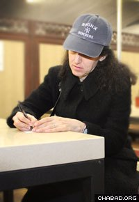 Judy Federbush composes her thoughts as she writes a note to be read at the Rebbe's resting place.