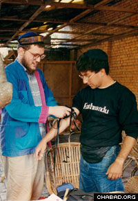 Rabbi Asi Spiegel helps a Jewish traveler in Nepal don the prayer boxes known as tefillin.