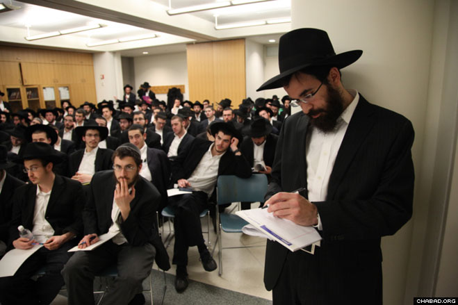 """Rabbi Schneur Najar, who coordinates with Rabbi Mendy Kotlarsky the """"Roving Rabbis"""" program run by Merkos L'Inyonei Chinuch, the educational arm of Chabad-Lubavitch, reviews documents before sending off 650 rabbinical students to locations around the globe."""