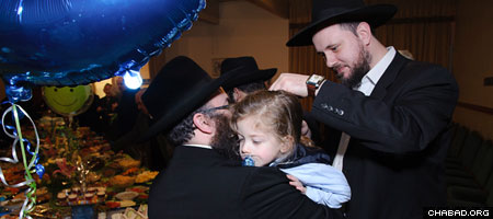 Rabbi Yitzchak Mendel Wagner, right, who only recently met Rabbi Aaron Lipsey, his Jewish Learning Network study partner of three years face to face, cuts a lock of his three-year-old son's hair at a traditional ceremony known as an upsherin.