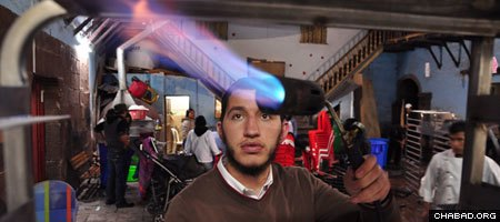 A visiting Chabad-Lubavitch rabbinical student uses a blowtorch to kosher kitchen equipment as part of Passover preparations in Cusco, Peru.