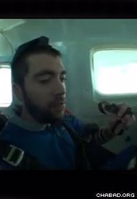 While wearing tefillin, student Michael Eisenberg concentrates on his prayers while ascending to the jump point.