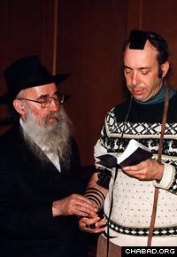 Rabbi Dovid Raskin helps a man don the Jewish prayer boxes known as tefillin. (Photo: Lubavitch Archives)