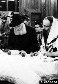 With the Rebbe, Rabbi Menachem M. Schneerson, of righteous memory, beside him, Rabbi Dovid Raskin, right, reads from the Torah during a weekly service at the synagogue in Lubavitch World Headquarters. (Photo: Rabbi Shlomo Friedman/Lubavitch Archives)