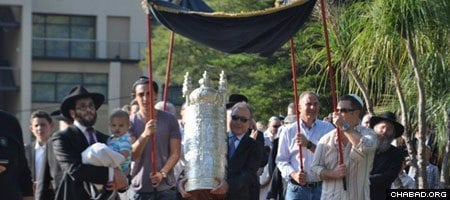 Celebrants parade a new Torah scroll through the streets of the Hyde Park suburb of Johannesburg.