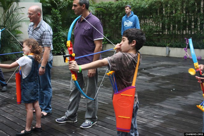 Children in Hong Kong practice their archery skills at a Lag B'Omer family event sponsored by the local Chabad House. Playing with bows has its roots in the tradition that, because of his righteousness, no rainbow – reminiscent of the Great Flood that destroyed the world – was seen during Rabbi Shimon bar Yochai's lifetime. Occurring 33 days after the beginning of Passover, Lag B'Omer commemorates the passing of Rabbi Shimon bar Yochai, the second-century mystic credited with authoring the Kabbalistic source text known as the Zohar.