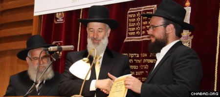 Israeli Chief Rabbi Yona Metzger, center, confers an ordination certificate on one of six graduating rabbis from Berlin's Yeshiva Gedola.