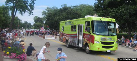 A synagogue on wheels known as a Mitzvah Mobile participates in an Independence Day parade in Northbrook, Ill.