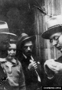 The Rebbe, left, reviews children's educational material with a young student activist. (Photo: Lubavitch Archives)