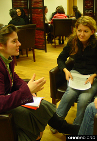 A Lubavitch seminary student studies a text of Chabad philosophy with college students in Vienna, Austria.