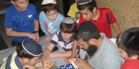 Yaacov leading the kids in a quiet game.