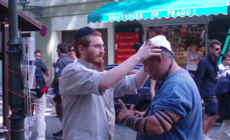A roving rabbi helping a Jew don tefillin on the streets of Old Prague a number of summers ago.