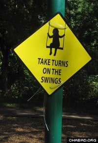 A sign reminds children to take turns.