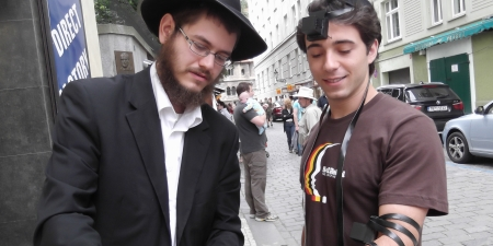 Hepling the boy born after the Rebbe's blessing into tefillin for the very first time in his life.