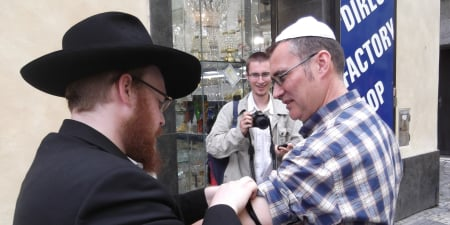 I help Robert into tefillin as his son watches proudly.