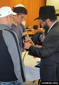 Rabbi Yossy Gordon, executive vice president of the Chabad on Campus International Foundation, helps a student don the prayer boxes known as tefillin.